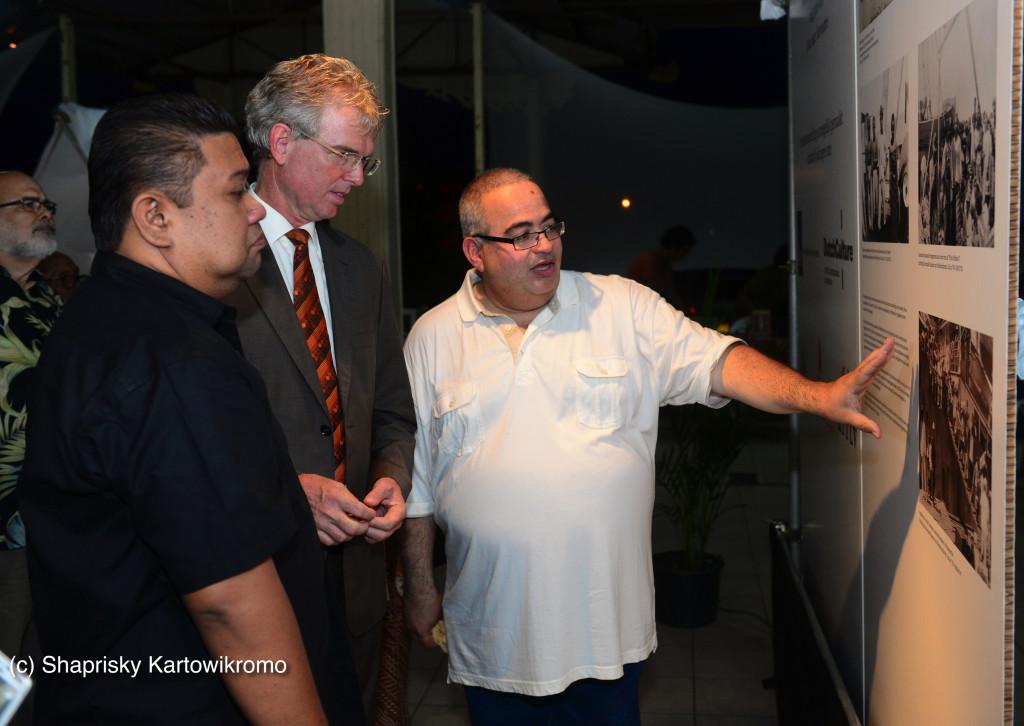 Ernst Noorman, de Nederlandse ambassadeur in Paramaribo, en Minister van Handel & Industrie Don Tosendjojo, worden rondgeleid door curator Peter Sanches
